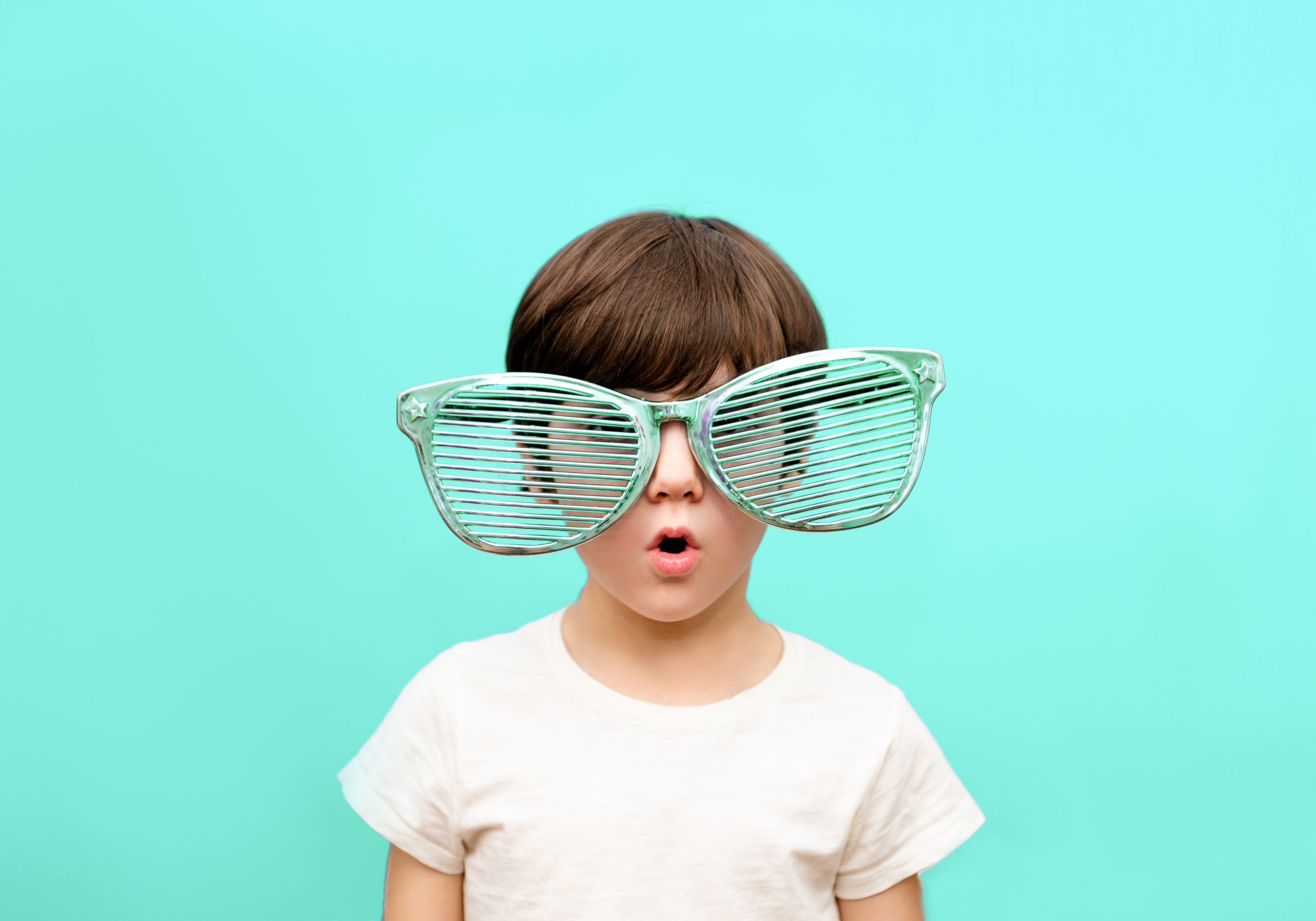 Cheerful little boy in big glasses express a surprised face isolated on blue background