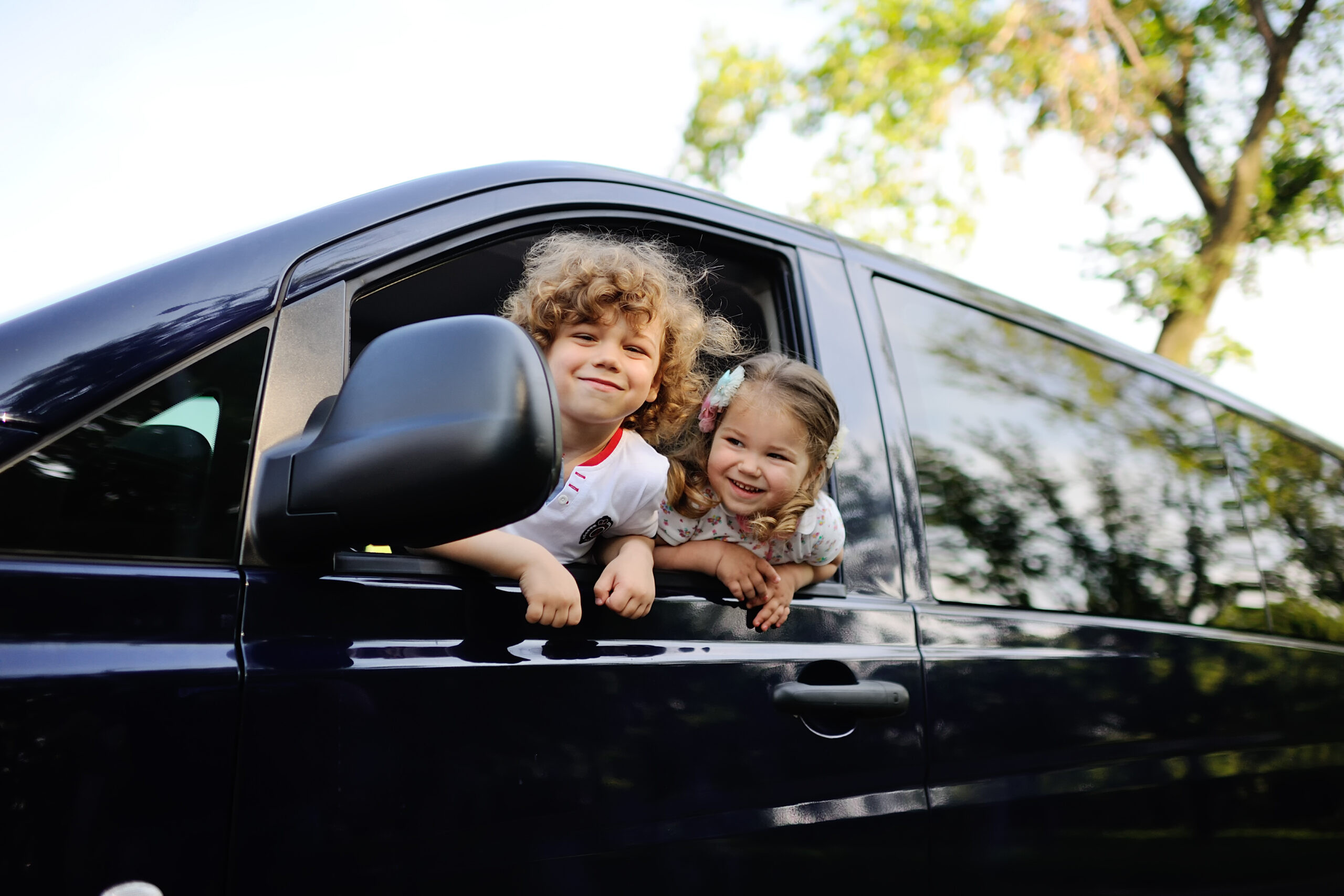 children look out from a car window.little boy and girl playing inside a minivan.family trip
